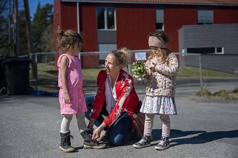 Ellen Elisabeth Tveiten sitoi tyttärensä Nannan kengännauhoja Stenbråtenin päiväkodin pihalla lähellä Osloa maanantaina 20. huhtikuuta, kun Norja alkoi avata päiväkotejaan. Mukana kuvassa myös toinen tytär Iselin.