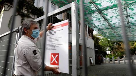 Eläintarhan työntekijä asetti tiedotusta Prahan eläintarhan portille perjantaina. Tšekkien hallitus sulki eläintarhat ja kielsi urheilu- ja kulttuuritapahtumat kahdeksi viikoksi koronaviruksen leviämisen ehkäisemiseksi.
