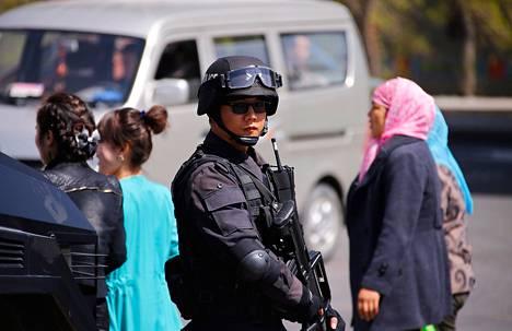 Poliisi vartioi kadulla toukokuussa, jolloin 79 ihmistä kuoli kahdessa erillisessä iskussa Urumqissa Xinjiangissa.
