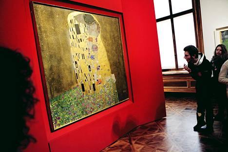 Gustav Klimt suutelee muusaansa Emilie Flögeä Suudelma-maalauksessa Belvedere-museossa.