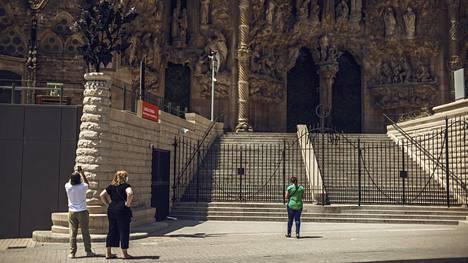Muutama turisti ihailee Sagrada Familian kirkkoa 20. kesäkuuta. Kirkko on yksi Barcelonan suosituimmista turistinähtävyyksistä. Suomalaiset pääsevät Espanjaan matkalle, mutta Suomen ulkoministeriö ei suosittele matkailua maahan ja sieltä palatessa suositellaan omaehtoista karanteenia.