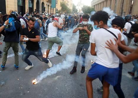Mielenosoittajat väistelivät poliisin ampumia kyynelkaasukranaatteja Beirutissa maanantai-iltana.
