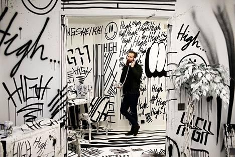 Jouni Väänänen hotelli Helkan huoneessa, jonka graffittitaiteilija Sheikki on maalannut täyteen high-tägiään.