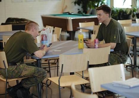 Eemeli Lehtonen (vas.) ja Roope Ritola odottavat pitsojensa valmistumista sotilaskodissa Upinniemessä ja tappavat aikaa puhelimella.