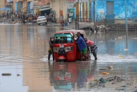Miehet työnsivät riksaansa sateiden jälkeen tulvivassa Somalian pääkaupungissa Mogadishussa 26. marraskuuta.