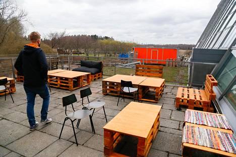 Rasmus Suikki ravintolan terassialueella. Taustalla häämöttävät Viikin pellot.