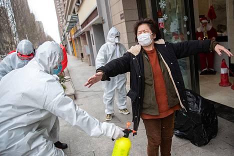 Covid-19-tauti lähti leviämään Kiinassa Wuhanin kaupungista. Maaliskuun alussa viruksesta toipuva nainen desinfioitiin kadulla ennen kuin hän siirtyi hotellikaranteeniin.