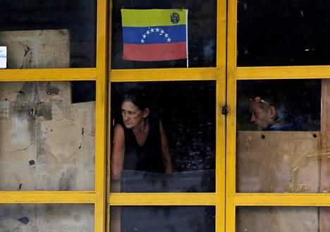 Pariskunta tarkkaili tilannetta ikkunan läpi torstain yleislakon aikana torstaina Venezuelan pääkaupungissa Caracasissa.