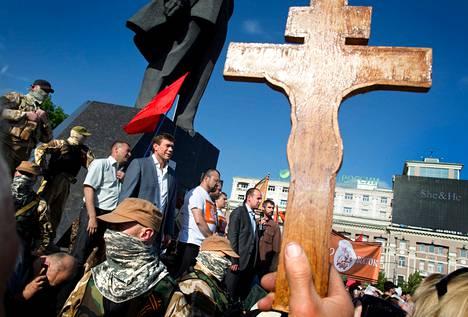 Venäjämieliset osoittivat lauantaina mieltä Lenin-aukiolla Donetskissa. Punaisen lipun alla puhuva harmaapukuinen mies on presidentinvaaleista vetäytynyt venäjämielinen poliitikko Oleg Tsarjov.