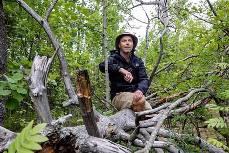 Helsinkiläinen luontoaktiivi Mika Välipirtti istui kaatuneen kelon päällä Helsingin Keskuspuistossa heinäkuussa.