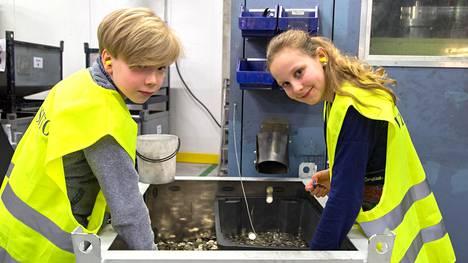 Koululaistoimittajat Juhana Waris ja Alma Parry ihastelevat upouusia, vielä lämpimiä kolikoita. Meluisassa hallissa korvat on hyvä suojata korvatulpilla.