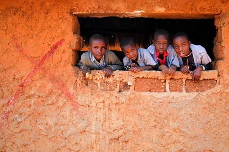 Mashimoni-koulun oppilaat katsovat koulun ikkunasta. Koulun seinässä oleva punainen risti kertoo koulun olevan purettavien rakennusten listalla.