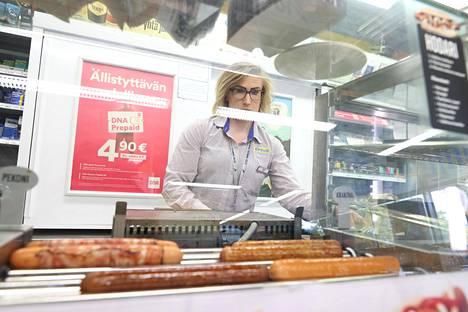 Merchant Riikka Halttunen fries sausages.  Halttunen likes that the job description is diverse.