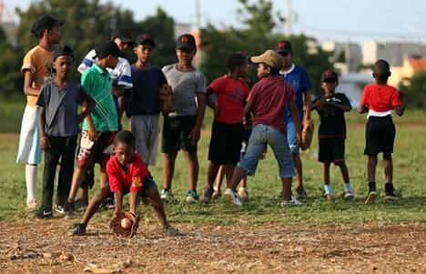 Joukko lapsia harjoitteli maahan osuvien baseball-lyöntien kiinniottamista San Pedro de Macorísin kaupungissa Dominikaanisessa tasavallassa lokakuussa 2014.