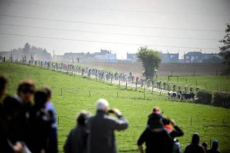 Yleisö seurasi maaseudulla Pariisi-Roubaix-kisaa pellolla.