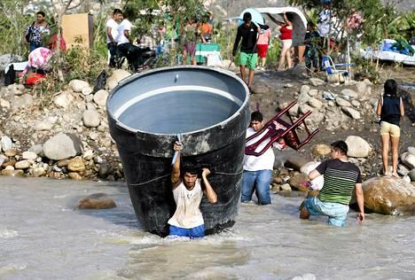 Ihmiset kantoivat omaisuuttaan rajan yli Venezuelasta Kolumbiaan Villa del Rosarion kylän lähellä tiistaina.