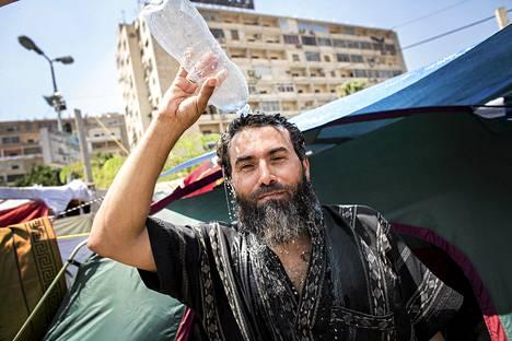 Abdelaziz Hanpi kaatoi vettä päähänsä, kun polttava aurinko kärvensä Muslimiveljeskunnan protestileiriä Kairossa sunnuntaina.