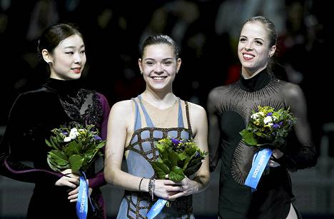 Yuna Kimin (vasemmalla) hymy jäi väkinäiseksi kukitustilaisuudessa. Vierellä Adelina Sotnikova ja Carolina Kostner.