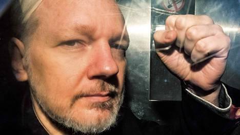 Julian Assange viittoo poliisiauton lasin läpi, kun häntä kuljetetaan pois oikeudenistunnosta 1. päivä toukokuuta 2019.
