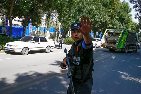 Kiinalaispoliisi viittilöi toimittajille tiesululla Xinjiangin maakunnassa syyskuussa 2018.
