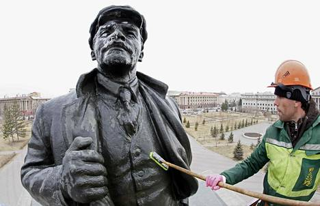 Kaupungin työntekijä pesee Vladimir Lenin patsasta siperialaisessa Krasnojarskissa perjantaina. Lauantaina Leninin syntymästä on kulunut 147 vuotta.