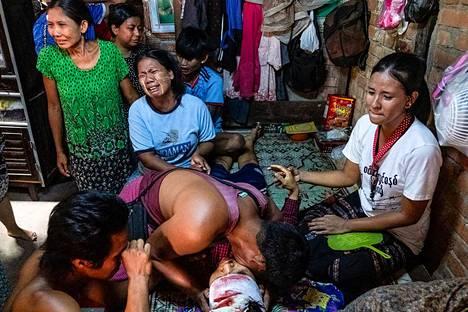 Sukulaiset surivat hallituksen vastaisiin mielenosoituksiin liittyneen poliisin ruumiin äärellä Yangonissa lauantaina. Kuva on välitetty kuvatoimisto AFP:lle Facebookin kautta.