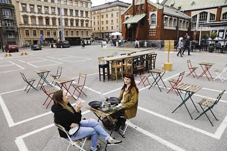 Johanna Karppinen (vas.) ja Lumi Orava lounaalla Hietalahden kauppatorilla. . Ruokapöydät on asetettu kirpputorin ruudukkoille.