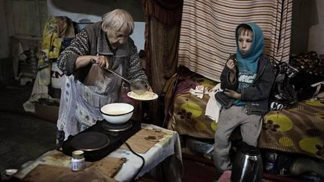 Marija-mummo, 86, lusikoi spagettia 9-vuotiaalle Sašalle. Mummo ja poika ovat asuneet pommisuojassa Donetskissa kodin tuhouduttua, eli sodan alusta lähtien.