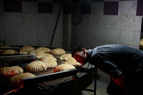 Syyrialaismies valvoo leipien paistumista Ghoutassa, Damaskoksen itäosissa. Leivät on tarkoitettu ruoka-avuksi kapinallisten hallinnassa olevaan Douman kaupunkiin.