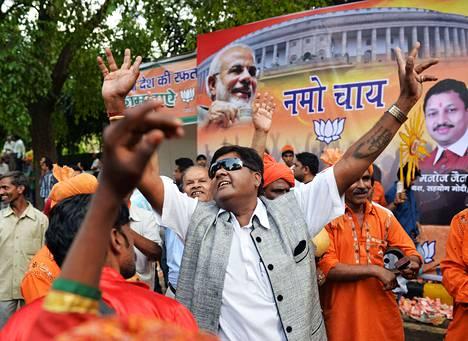 BJP:n ja Narendra Modin kannattajat tanssivat perjantaina puolueen päämajan edustalla Delhissä.