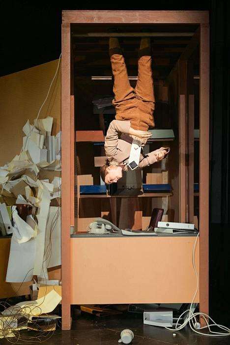 Esitys tapahtuu konttorissa, jossa esiintyjät asettuvat ryhmäakrobatiaa vaativiin asentoihin.