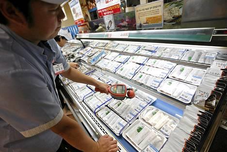 Kaupan työntekijä mittasi kalatiskin tuotteiden radioaktiivisuutta Soulissa perjantaina.