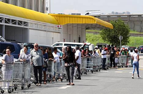 Ihmiset jonottivat ruokakauppaan Johannesburgissa Etelä-Afrikassa tiistaina.