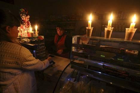 Asiakkaat kävivät ostoksilla kynttilänvalossa Krimillä Simferopolin kaupungissa sunnuntaina.