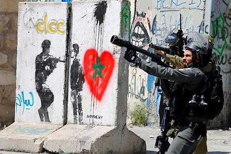 Israelilaiset mellakkapoliisit yrittävät rauhoittaa palestiinalaisia mielenosoittajia Betlehemissä. Kadun betoniesteissä näkyy katutaiteilija Banksyn graffiti.
