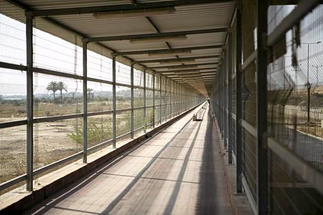 Päästäkseen Israelista Gazaan on käveltävä noin kilometrin verran tiukasti aidattua kävelytietä.