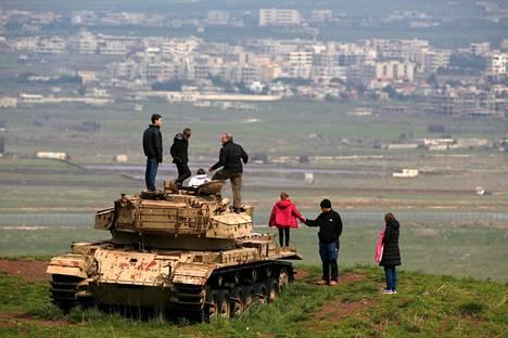 Golanin kukkuloihin tutustuvia ihmisiä vanhan israelilaistankin päällä Majdal Shamsissa lauantaina. Taustalla näkyy syyrialainen Qunaitran kaupunki.