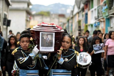 Bändikaverit kantoivat mutavyöryssä kuollutta ystäväänsä Guatemalan pääkaupungissa Guatemalassa sunnuntaina. Vyöryssä on kuollut ainakin 120 henkeä mutta yli kolmesataa on vielä kateissa.