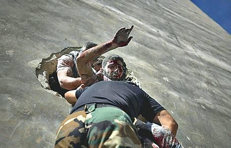 Kapinallinen siirsi haavoittunutta taistelijaa turvaan rakennuksen seinässä olevasta aukosta Aleppossa keskiviikkona.
