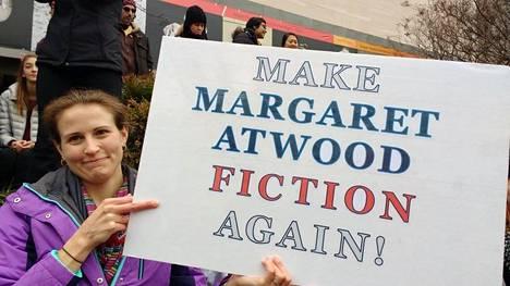 Margaret Atwoodista on tullut yksi presidentti Donald Trumpin vastaisten mielenosoitusten symboleja. Mielenosoittajan kyltti toivoi Torontossa, että Atwoodista tulisi taas fiktiota.
