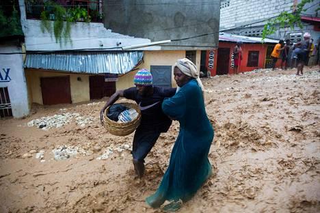 Torikauppiaat pakenivat hirmumyrsky Lauran aiheuttamaa tulvaa Petition villessä Haitilla viime sunnunstaina.