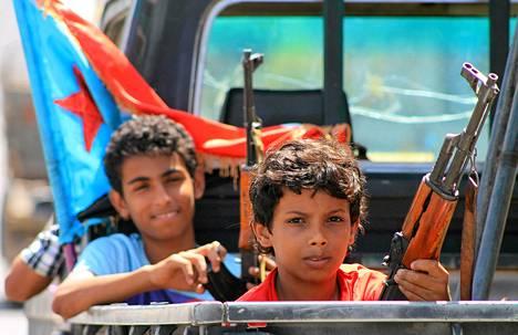 Aseistetut jemeniläislapset sunnuntaina Jemenin rannikkokaupungissa Adenissa.
