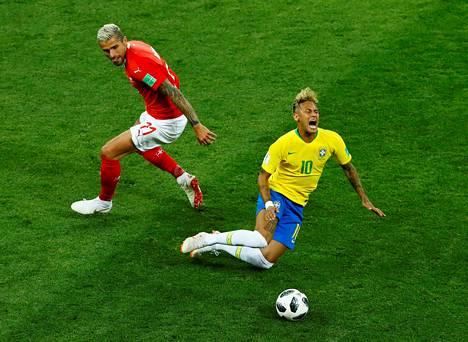 Brasilian Neymar kaatuu taistellessaan pallosta Sveitsin Valon Behramia vastaan.