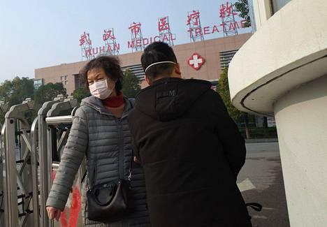 Ihmisiä poistumassa kiinalaisesta Wuhanin sairaalasta, jossa kuoli ensimmäinen uhri uuden viruksen aiheuttamaan keuhkokuumeeseen tammikuun alussa.