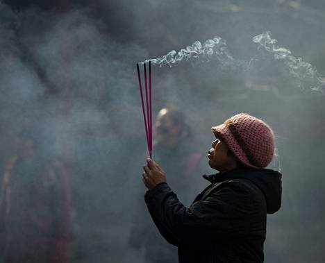 Kiinalaisnainen poltti suitsukkeita Pekingissä uuden vuoden juhlien alla.