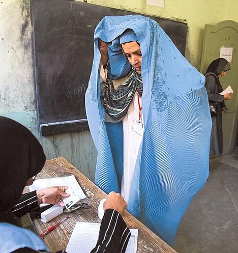 Nainen raotti burkaansa osoittaakseen henkilöytensä vaalivirkailijalle Heratissa Länsi-Afganistanissa parlamenttivaalien äänestyksessä syyskuussa 2010. Väkivalta ja epäselvyydet ovat varjostaneet Afganistanissa Hamid Karzain kausilla järjestettyjä vaaleja.