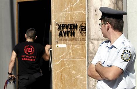 Kreikkalainen poliisi partioi Kultainen aamunkoitto -puolueen toimiston ovella Ateenassa keskiviikkona.