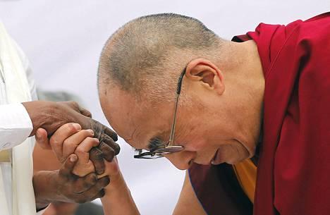 Dalai Lama pitelee leprapotilaan kättä New Delhissä maaliskuussa.