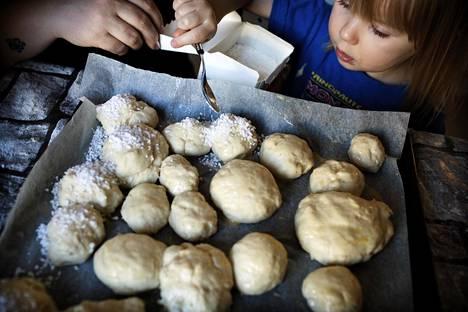 Maanantaina Laaksosen perhepäivähoitoryhmä leipoi laskiaisen kunniaksi pullia. Lumi Kiefer, 3, sirotteli pullan päälle sokeria.