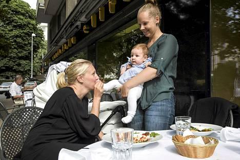 Mirva Puurtinen (vas.) ja Jonna Kukkonen lounastivat ravintola Eliten terassilla pienten lastensa kanssa. Puurtinen ja Kukkonen ovat molemmat yhtä mieltä siitä, että tilaisuus ja paikka ratkaisevat ravintola-asun valinnan. Kukkosen sylissä istuu tytär Selma Arzoglou.